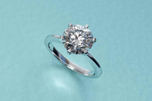 närbild solitaire diamant förlovningsring på turkos bakgrund - förlovningsring bildbanksfoton och bilder