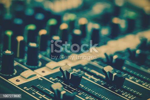 istock Closeup some part of audio mixer, vintage film style, music equipment concept 1007273532