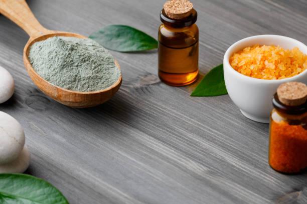 close-up kosmetik wellnessprodukte - lehm, öl und meer salz auf einem hölzernen hintergrund. - steingut geschirr stock-fotos und bilder