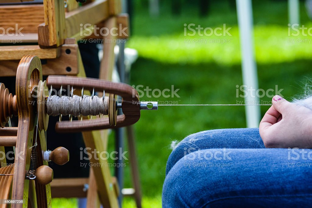 Close-Up Spinning Yarn on a Wheel stock photo