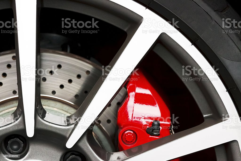 Closeup sports car alloy wheel with red carbon ceramic brake stock photo