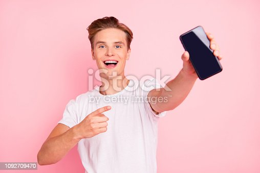 istock Closeup studio photo portrait of adorable confident dreamy cute handsome delightful optimistic with open mouth boy showing monitor to camera isolated background 1092709470