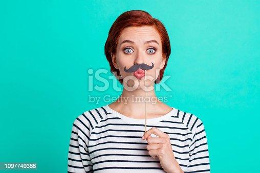 istock Closeup studio photo portrait of joking humorous pretty glad nice lady she her holding showing fake beard under nose isolated vivid turquoise background 1097749388
