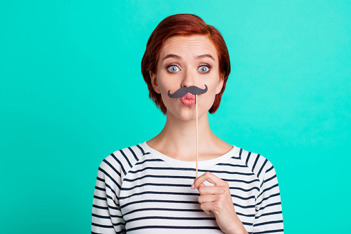 istock Closeup studio photo portrait of joking humorous pretty glad nice lady she her holding showing fake beard under nose isolated vivid turquoise background 1097749388