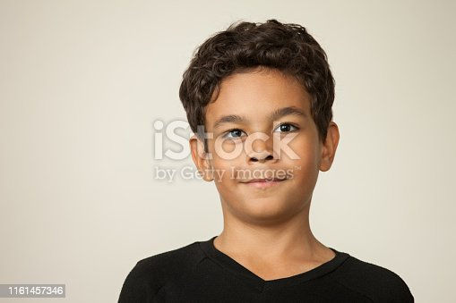 Closeup studio portrait of a 12 year old boy on a beige background