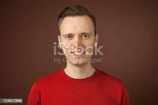 close-up studio portrait of a 24 year old man with brown hair in a red sweater on a brown background