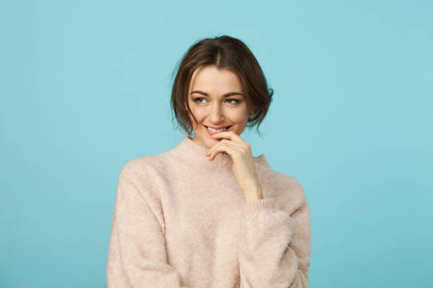 close-up studio portrait of a young attractive woman 30 years old in a beige sweater on a blue background - mano sul mento foto e immagini stock
