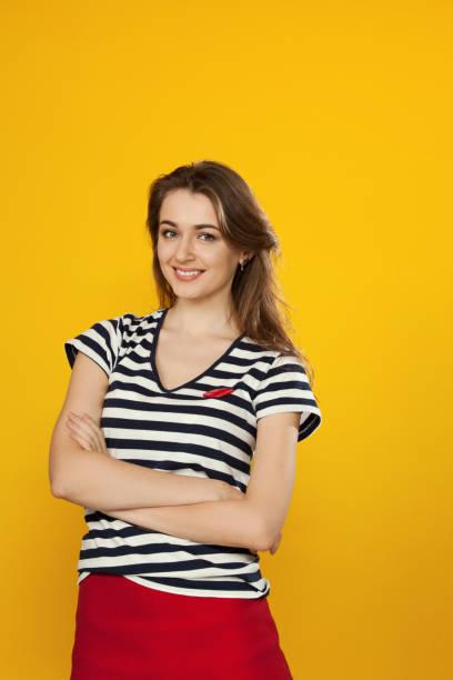 close-up studio-porträt einer jungen attraktiven frau 30 jahre alt auf gelbem hintergrund - lange gestreifte röcke stock-fotos und bilder