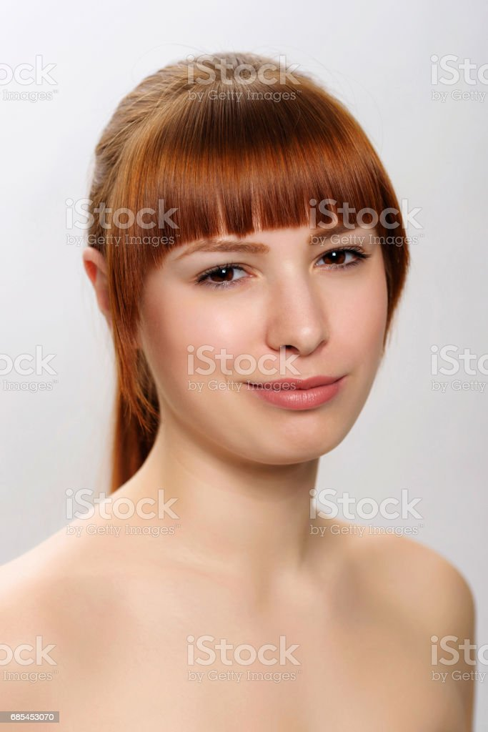 close-up studio portrait of a young beautiful woman demonstrating a contemptuous smile foto de stock royalty-free