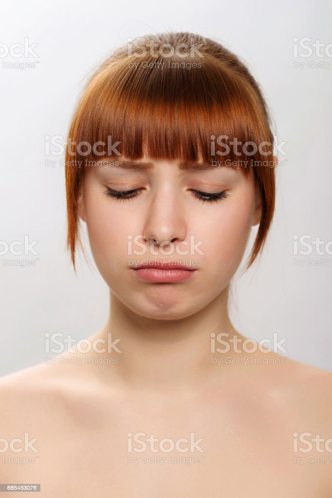 close-up studio portrait of a young beautiful woman demonstrating an emotion of sadness foto de stock royalty-free