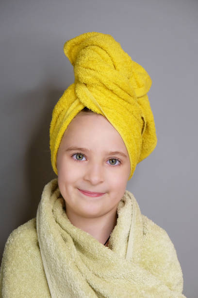 Close-up studio portrait of beautiful smiling little girl with green eye after shower. stock photo