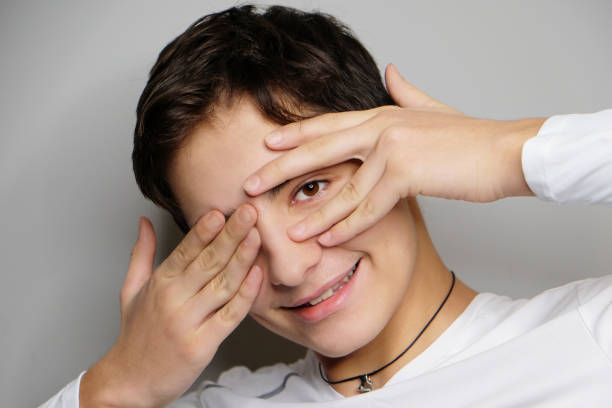 Close-up studio portrait of beautiful smiling teenage boy isolated on grey background. stock photo