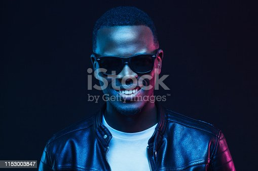 1095939686istockphoto Close-up studio portrait of smiling african american male model wearing trendy sunglasses and leather jacket 1153003847