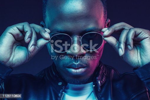 1095939686istockphoto Close-up studio shot of african american male model wearing trendy sunglasses and leather jacket 1125110804