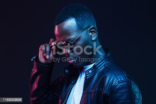 1095939686istockphoto Close-up studio shot of african american male model wearing trendy sunglasses and leather jacket 1153003835