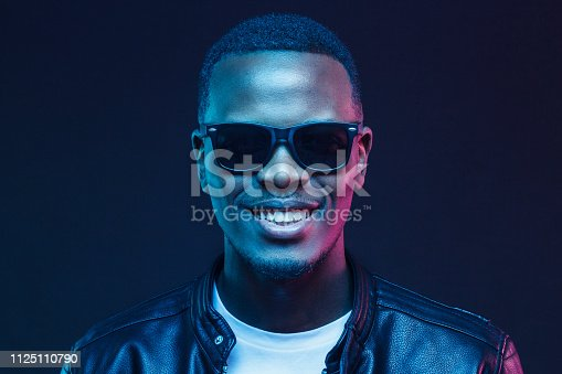 1095939686istockphoto Close-up studio shot of smiling african american male model wearing trendy sunglasses and leather jacket 1125110790
