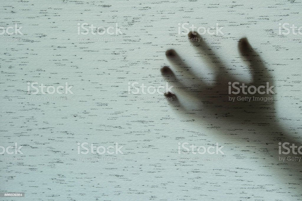 Closeup surface shadow of hand behind gray fabric curtain textured background with copy space in horror concept stock photo
