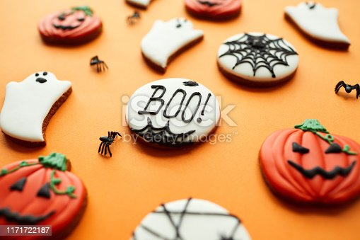 Close-up sweet sugar Halloween cookies with glaze, focus on Boo inscription written on cookie