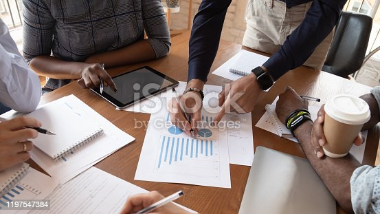 987123762 istock photo Closeup table financial statistics and diverse businesspeople hands working together 1197547384