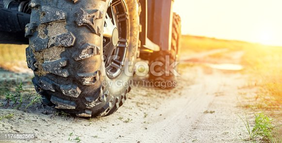Close-up tail view of ATV quad bike on dirt country road at evening sunset time. Dirty wheel of AWD all-terrain vehicle. Travel and adventure concept.Copyspace.Toned.