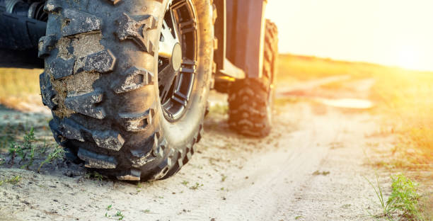 close-up tail view of atv quad bike on dirt country road at evening sunset time. dirty wheel of awd all-terrain vehicle. travel and adventure concept.copyspace.toned - bike tire tracks foto e immagini stock