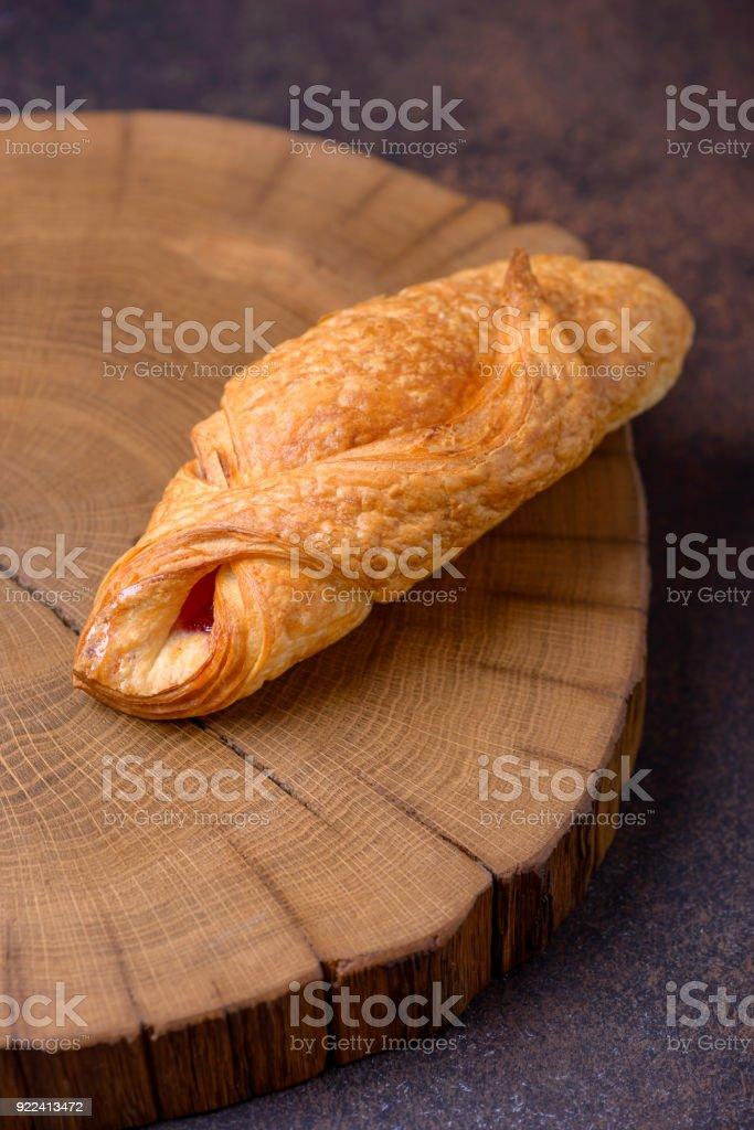 Closeup tasty croissant on cutting board stock photo
