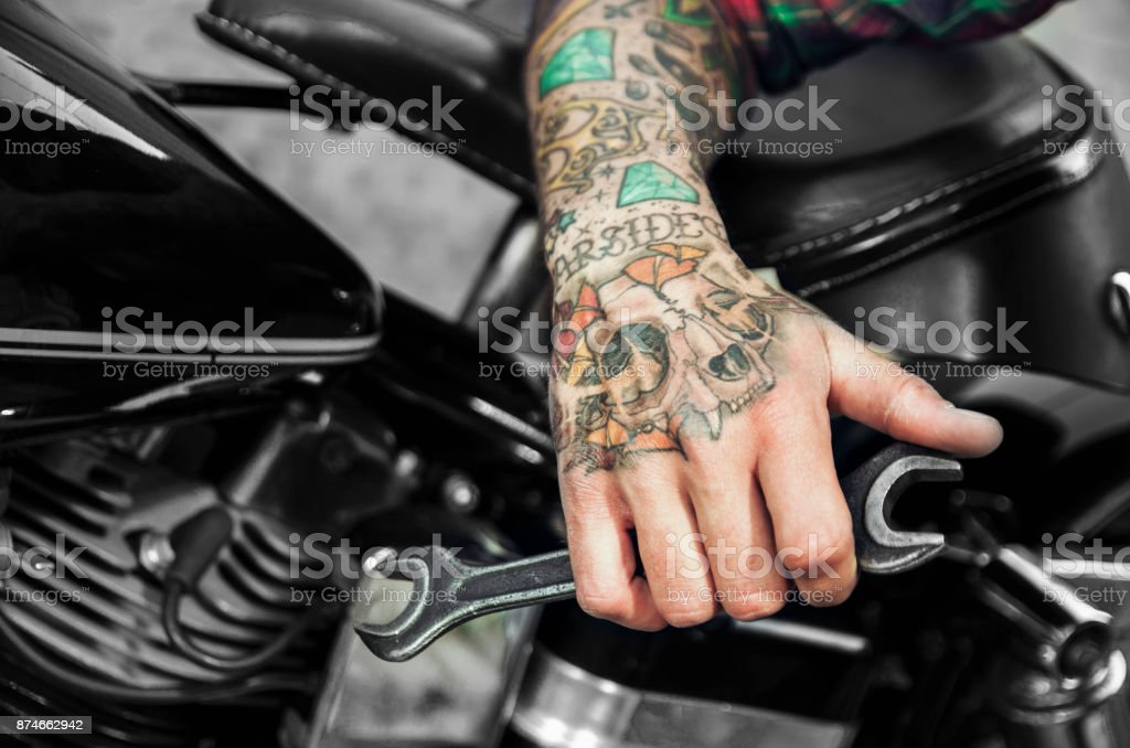 4a088f33f Closeup, tattooed man hand holding wrench, motorcycle in background - Stock  image .