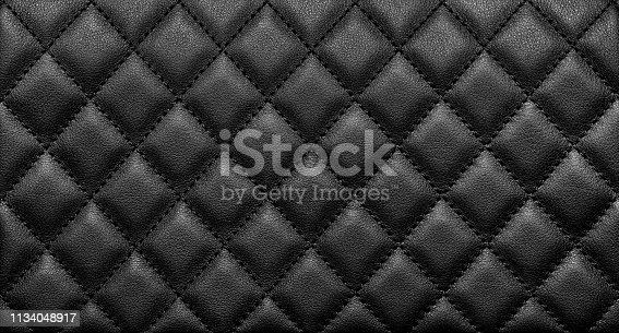 Close-up texture of genuine leather with black rhombic stitching. Luxury background