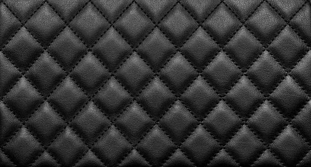 Close-up texture of genuine leather with black rhombic stitching stock photo