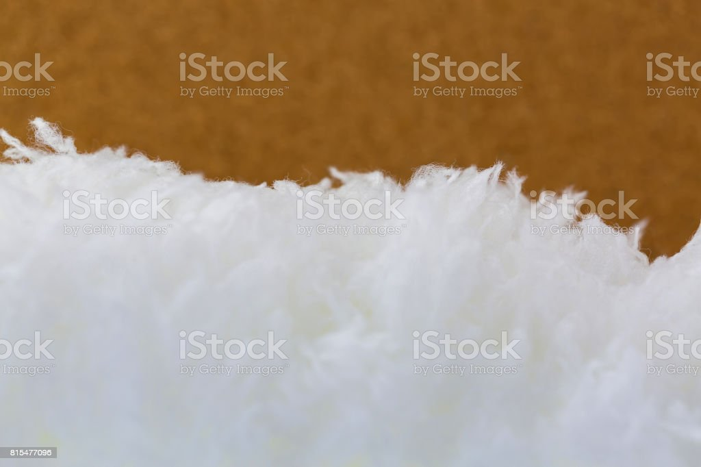 Closeup texture of soft fluffy white fur microfiber fabric on blurred brown cork background stock photo