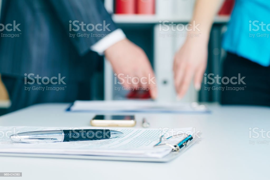 Close-up the pen lies on the documents. Business people hands pointing analyzing at the documents on the background. Teamwork successful meeting royalty-free stock photo