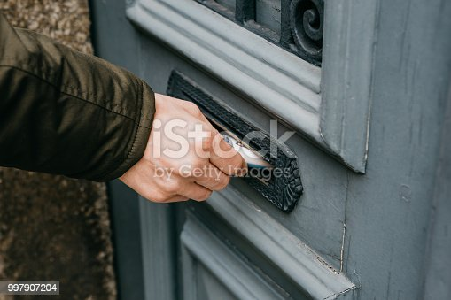 istock Close-up. The postman puts a letter or newspaper or magazine in the mailbox at the door of a residential building or a person puts a brochure with advertising 997907204