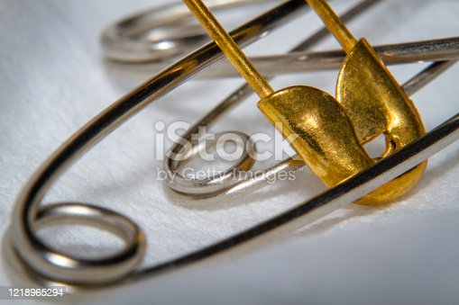 Close-up the smaller golden color safety pin in between variation of the regular safety pin simple spring mechanism