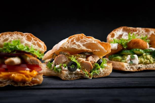 Closeup three different appetizing sandwiches or burgers on wooden picture id1221397734?b=1&k=6&m=1221397734&s=612x612&w=0&h=vnw0a6bq0kijxfnolcupvzgrztqjnghs7t9gqsnybum=