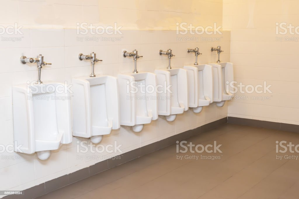 Closeup tiles wall in the toilet of man with toilet view by urinals and small room , interior at the old toilet background in black and white tone , interior of toilet in the office stock photo