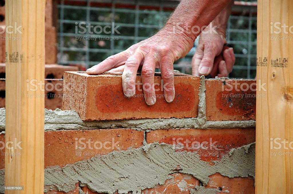Close-up to construction worker laying bricks with cement royalty-free stock photo