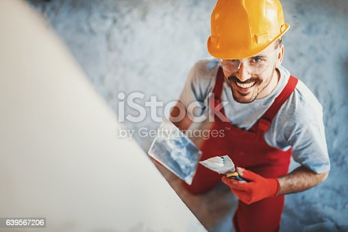Closeup top view of a construction worker finishing a facade in an interior drywall. He's smiling and looking at camera. Wearing red uniform and yellow work helmet.