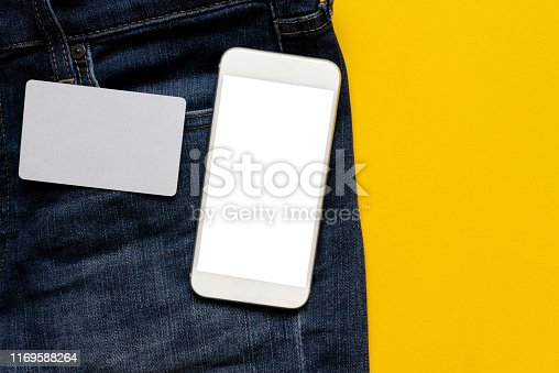 closeup top view of blank credit card and smartphone with clipping path isolated white screen (you can add content) on modern jean denim over yellow color background with copy space for design of trendy lifestyle fashion concept