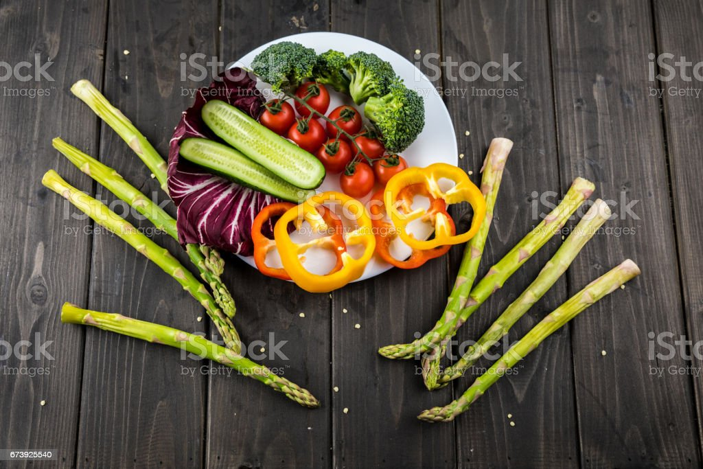 Close-up top view of fresh vegetables on plate on rustic wooden background photo libre de droits