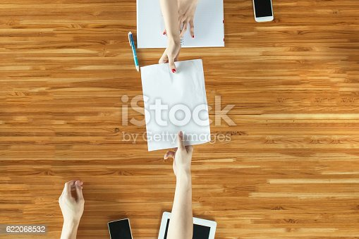 istock Closeup Top View of People handing out documents 622068532