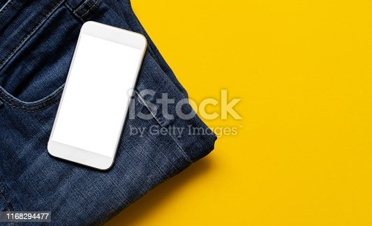closeup top view of smartphone with clipping path isolated white screen (you can add content) on modern jean denim over yellow color background with copy space for design of trendy lifestyle fashion concept