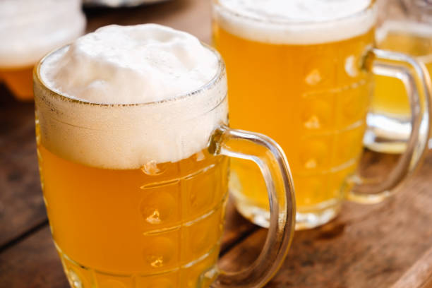 close-up two cold beers with foam and drops. - german culture stock pictures, royalty-free photos & images