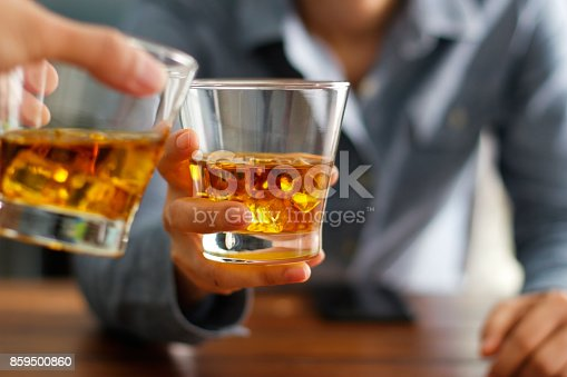 istock Close-up two men clinking glasses of whiskey drink alcohol beverage together at counter in the pub 859500860