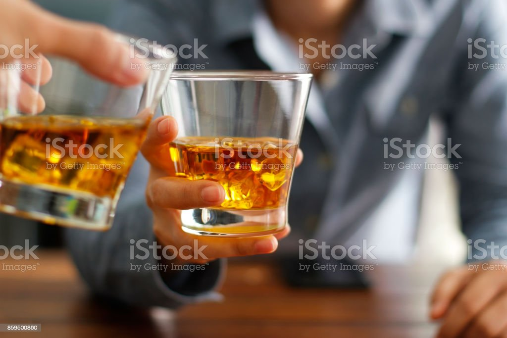 Close-up two men clinking glasses of whiskey drink alcohol beverage together at counter in the pub стоковое фото