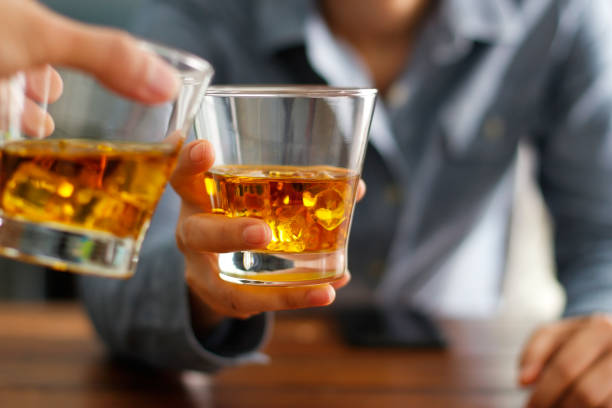 Close-up two men clinking glasses of whiskey drink alcohol beverage together at counter in the pub stock photo
