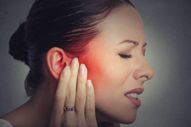 Closeup up side profile sick female having ear pain touching her painful head stock photo