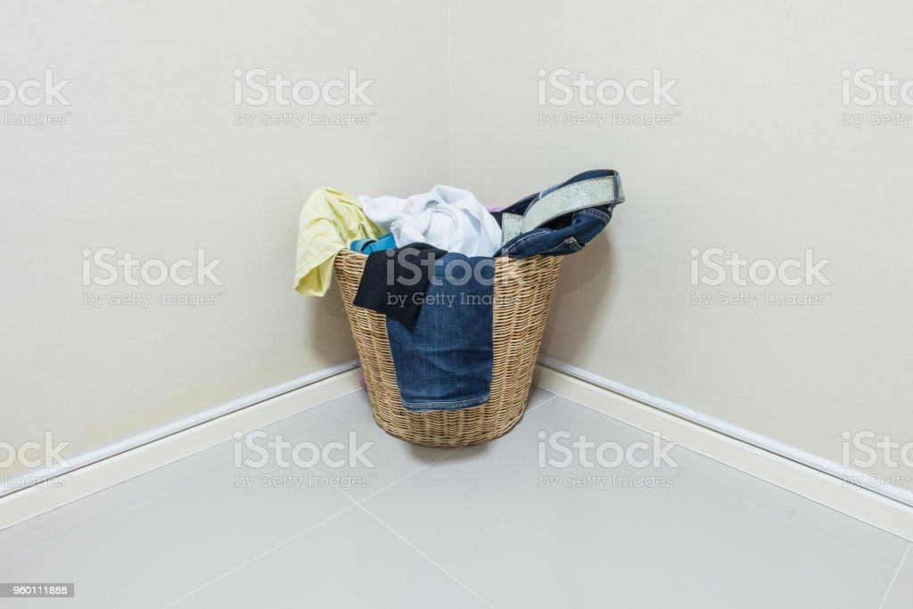 Closeup used clothes in wood basket at corner in room stock photo