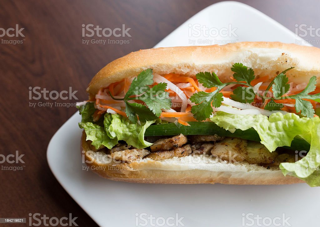 Close-up Vietnamese Bahn mi on white plate and wooden table stock photo