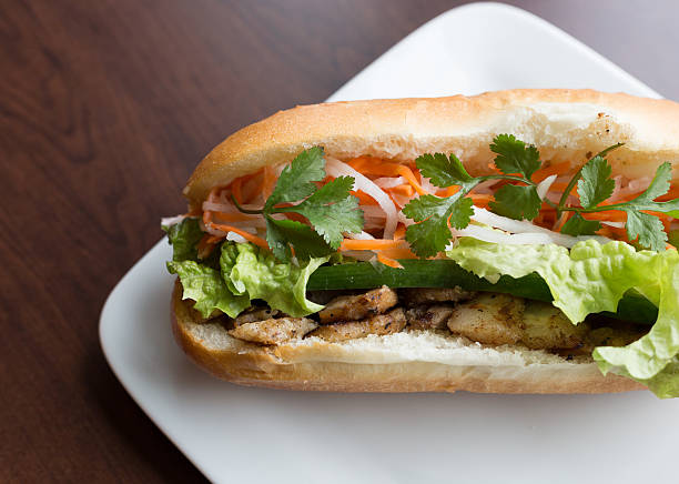 Close-up Vietnamese Bahn mi on white plate and wooden table A healthy sub sandwich / Vietnamese banh mi filled with meat and healthy veggies bánh mì sandwich stock pictures, royalty-free photos & images