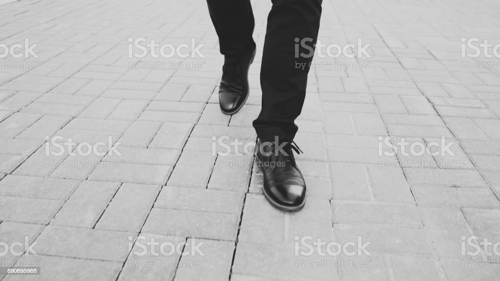 Closeup view businessman in shoes walking ahead sidewalk at street stock photo